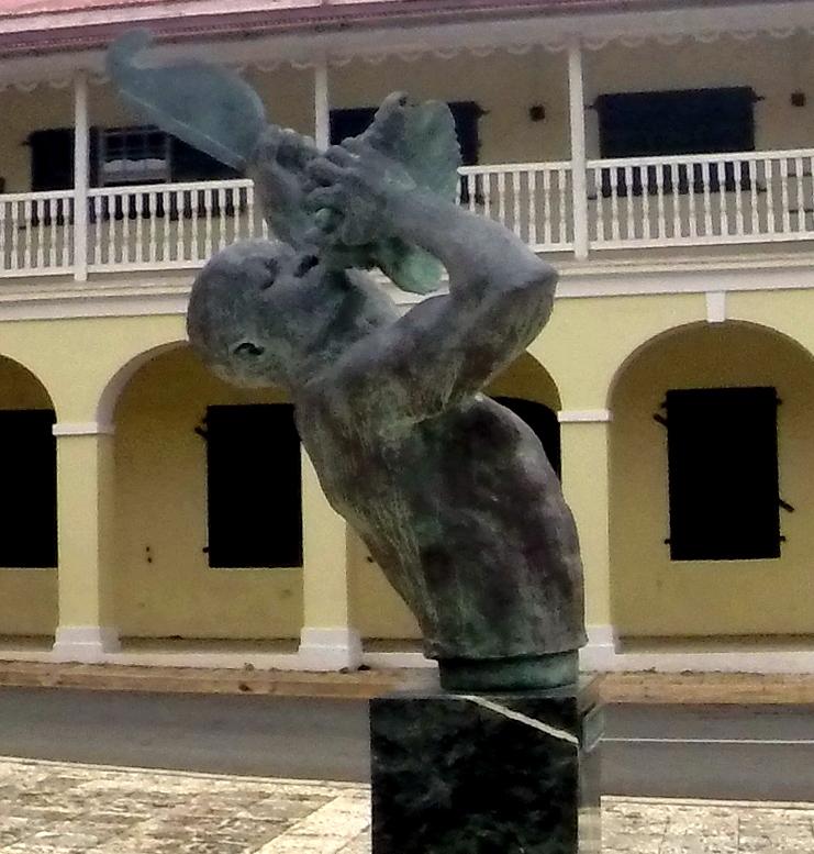 Statuen 'Freedom' symboliserer en slave der blæser til oprør i en konkylie med den ene hånd og med en sukkerkniv i den anden. Statuen er opstillet på alle tre Vestindiske øer, og endnu en er givet i gave til Danmark i 2017. Gekko Medieproduktioner.